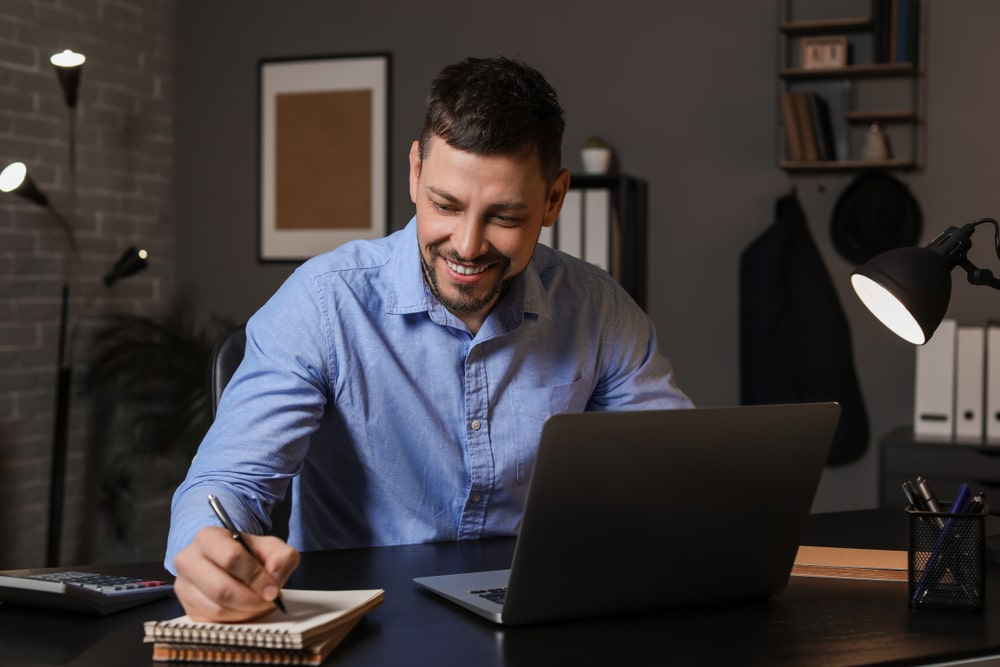 Man making notes while on laptop presenting online