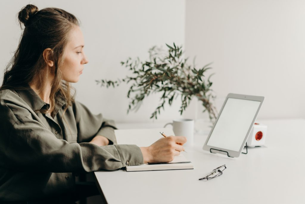 Young woman taking notes on webinar